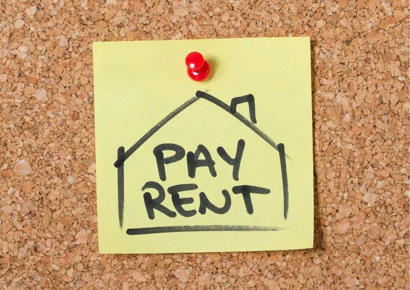 Cork board with sign saying pay rent