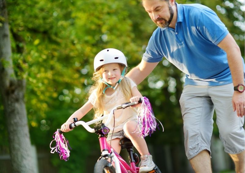 Father helping daughter on pushbike