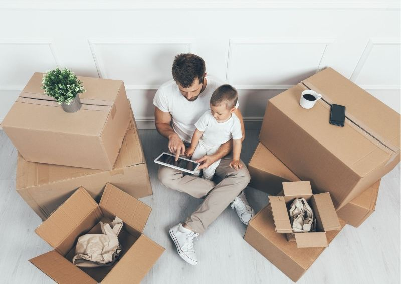 Man with Child looking a tablet while packing up their home