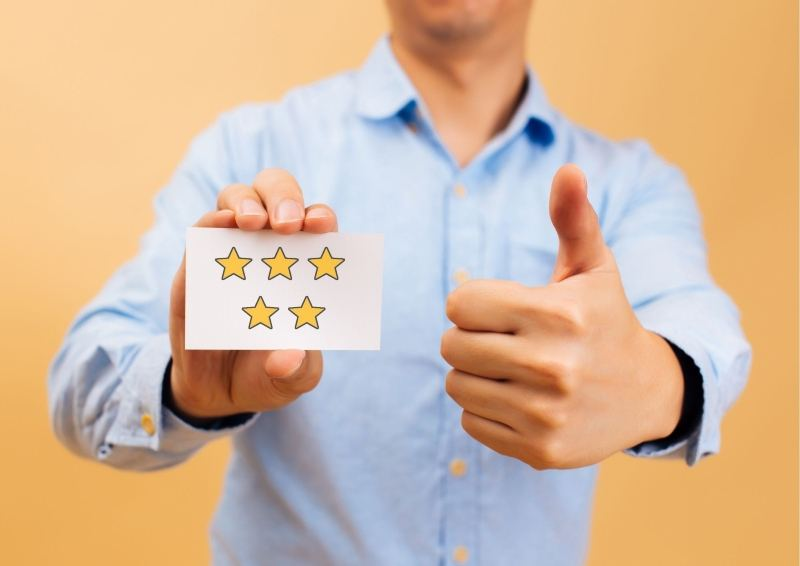 Person Holding a piece of paper with 5 stars on it.