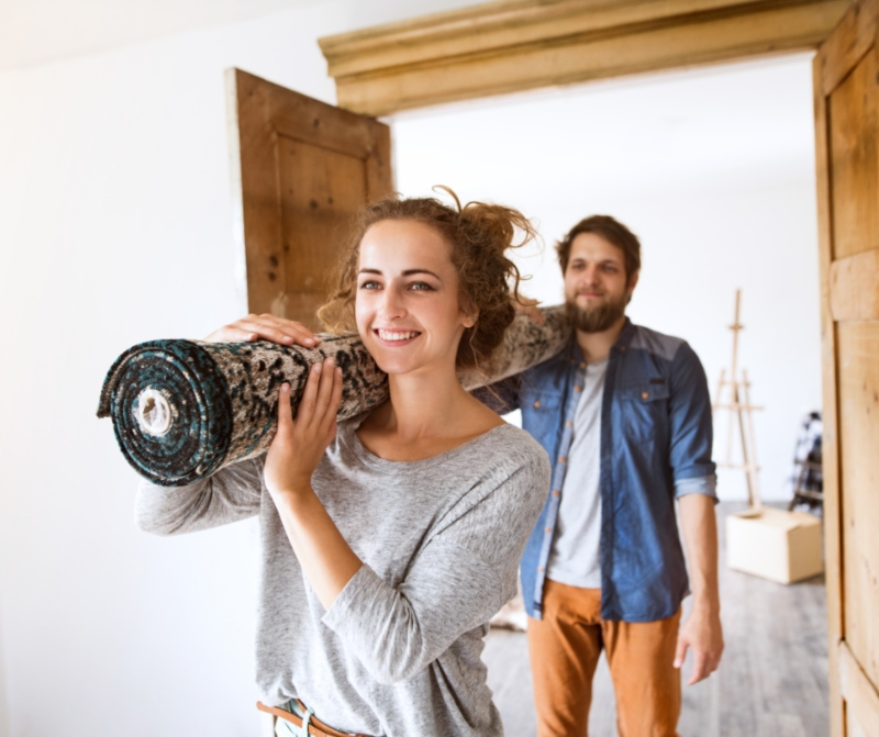 Couple carrying a rug for the new home