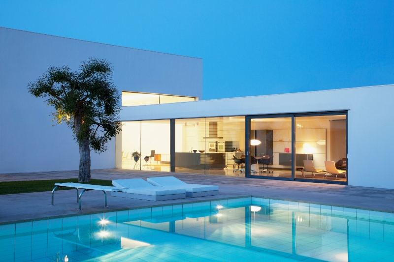 Looking across a swimming pool at a designer home
